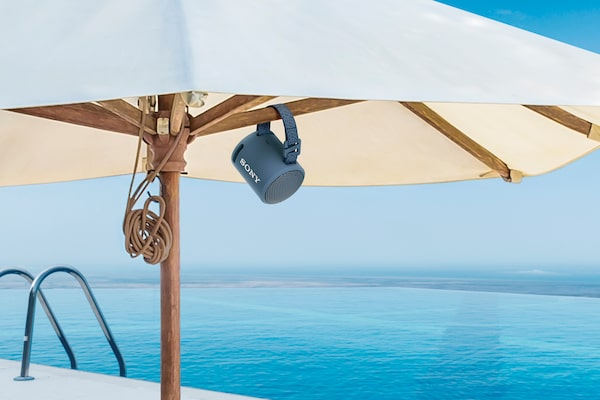 Slika prijenosnog bežičnog EXTRA BASS(TM) zvučnika XB13 prikvačenog na suncobran na tropskoj plaži.