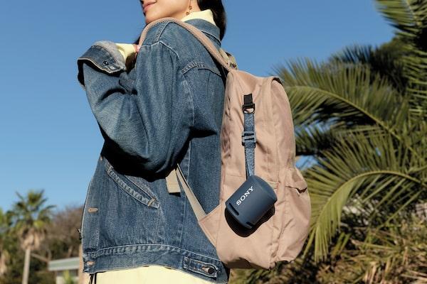 Slika žene s ruksakom za koji je prikvačen prijenosni bežični EXTRA BASS(TM) zvučnik XB13.