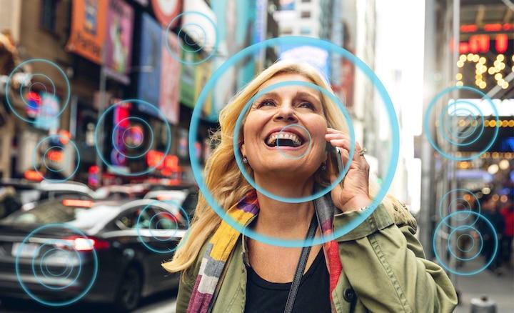 Žena na punoj ulici pokazuje kako Voice Zoom 2 olakšava slušanje govora